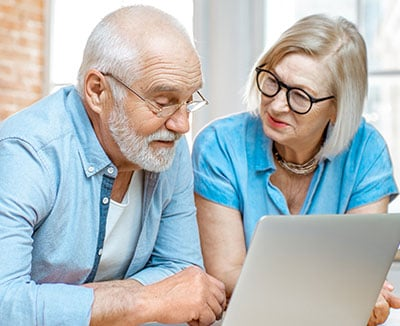 older couple scheduling vaccine on laptop