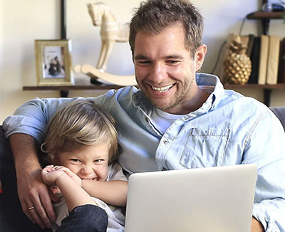 man and son using laptop at home